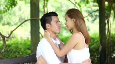 Asian couple sitting intimately in a park — Stock Video