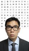 Asian man overwhelmed by social media symbols — Stock Photo