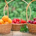 Fresh organic fruits in wicker baskets — Stock Photo #74952895