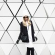 Glamorous blonde standing at the wall. Urban fashion black and w — Stock Photo #54627945