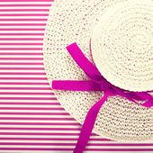 White straw sunhat on a striped magenta background — Stock Photo