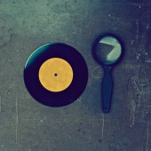 Vinyl record and magnifier on wooden table — Stock Photo