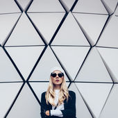 Glamorous blonde standing at the wall. Urban fashion black and w — Stock Photo