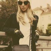 Stylish urban blonde. Female clutch and leather gloves and fashi — Stock Photo