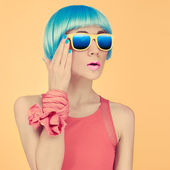 Fashion lady surprise in a blue wig and sunglasses on bright yel — Stock Photo