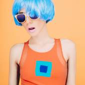 Fantastic party fashion lady in blue wig and glasses on yellow b — Stock Photo