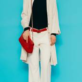 Fashion lady in stylish white clothes. White trousers and raincoat with red accessories — Stock Photo