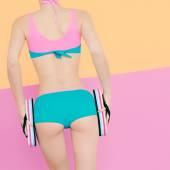 Flicka i Sport baddräkt håller i händerna sandaler vit bakgrund — Stockfoto