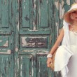 Model against vintage door in white dress and stylish accessorie — Stock Photo #74046931