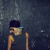 Stylish blonde in fashionable glasses and a cap. Urban fashion s — Stock Photo