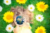 Child holding Earth planet in hands — Stock Photo