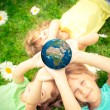 Children holding Earth planet in hands — Stock Photo #68857241