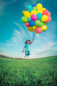 Child with toy balloons in spring field — Stock Photo