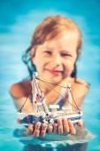 Child holding toy sailing boat — Stock Photo