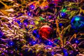 Snow covered Christmas tree and colorful decoration balls — Stockfoto