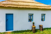 View of the peasant house with whitewall and reed roof. A door a — Stock Photo