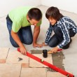 Man and boy laying ceramic floor tiles — Stock Photo #54278949