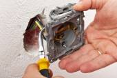 Electrician hand mounting a wall fixture — Stock Photo