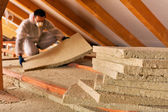 Man laying thermal insulation layer under the roof — Stock Photo