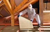 Man with rockwool panel installing insulation layer — Stock Photo