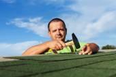Man finishing installing the bitumen roof shingles — Stock Photo