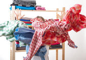 Woman throws a pile of clothes, isolated on white — Stock Photo