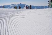 Fresh snow groomer tracks on a ski piste — Stock Photo