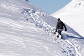 Snowboarder climbing a snowy mountain — Stock Photo