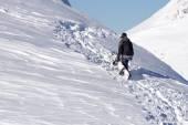 Snowboarder climbing a snowy mountain — Stock fotografie
