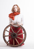 Young woman with an old wagon wheel — Stock Photo