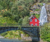 Red wooden Hous in front of a Waterfall in Norway — Stock Photo
