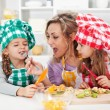 Woman and little girls preparing a fruit salad — Stock Photo #52340901