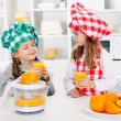 Little chef girls tasting the orange juice they made — Stock Photo #52340931