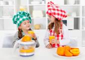 Little chef girls tasting the orange juice they made — Stock Photo