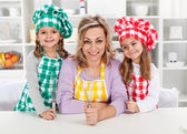Woman and her little helper chefs — Stock Photo