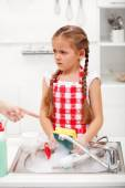 Sulking little girl doing the dishes — Stock Photo
