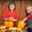 Kids carving their pumpkin jack-o-lanterns — Stock Photo #53479891