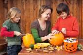 Woman helping kids to carve their Halloween jack-o-lantern — Stock Photo