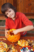 Boy preparing for Halloween - carving a jack-o-lantern — Stock Photo