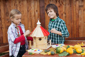 Kids painting a bird house — Stock Photo