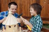 Father and son building a bird feeder — Stock Photo