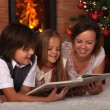 Family reading stories at Christmas time — Stock Photo #56249607