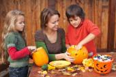 Woman helping kids to carve jack-o-lanterns — Stock fotografie