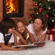 Family reading a story at Christmas time — Stock Photo #57808159