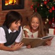 Kids reading a book - in front of the Christmas tree — Stock Photo #57808241