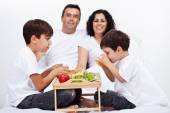 Familia desayunando en la cama — Foto de Stock