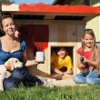 Happy kids painting the doghouse — Stock Photo #62091269