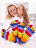 Woman and little girl wearing funny socks — Stock Photo