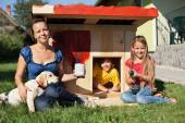 Happy kids painting the doghouse — Stock Photo