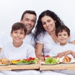 Happy family having breakfast in bed — Stock Photo #62909159